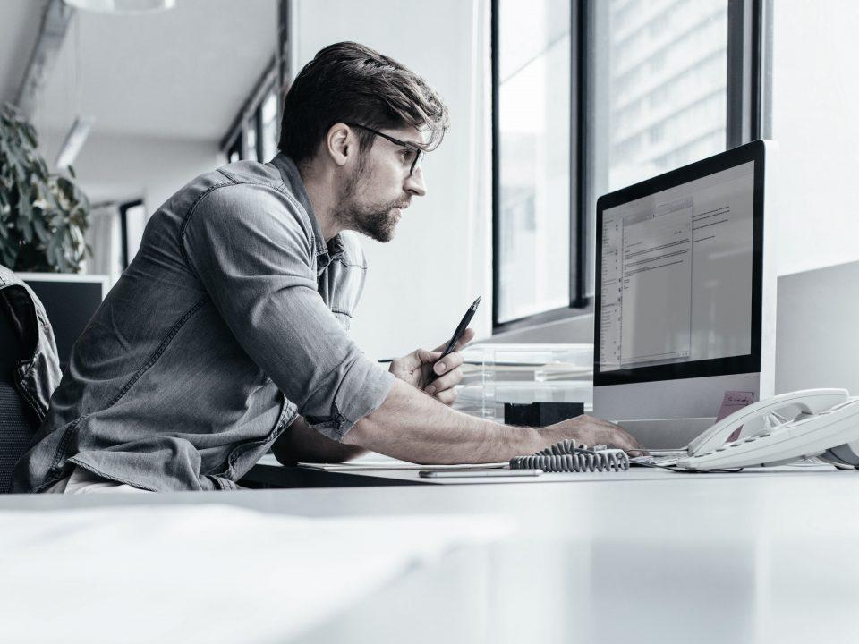 Ung mand følger konference på computer